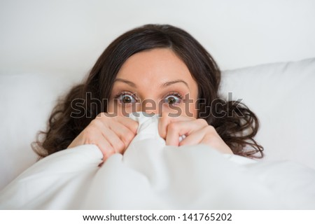 Beautiful scared young girl hides her face in bed and looking at camera with wide eyes - stock photo