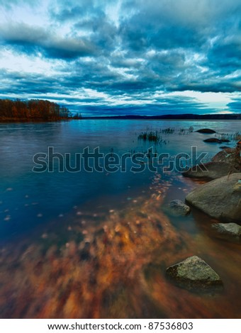 Beautiful scene from canada with orange leafs moving in the water. Hdr and slow shutter speed photography.