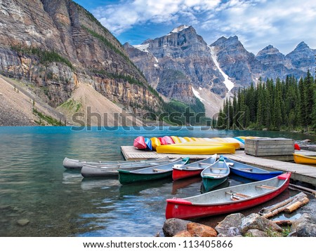 Beautiful Scene in one of the Rocky Mountain Lakes - Moraine Lake, Banff National Park - Canada. View of canoes on the dock by the lodge. - stock photo