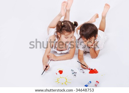 Beautiful scene of a girl and boy laying and playing with colors on ground - stock photo