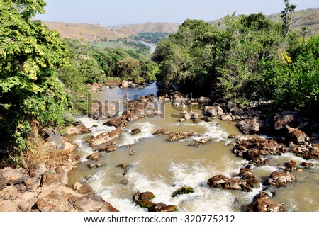 Beautiful Scene of a River Running over Rocks and Disappearing into the Distance, forming a Green Line of Vegetation in the Desert Mountains - stock photo