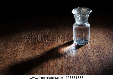 Beautiful scene of an empty vintage glass bottle isolated on a wooden background.  - stock photo