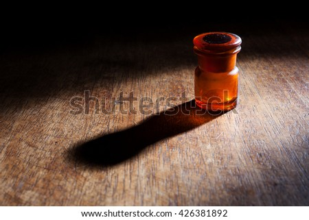 Beautiful scene of an empty vintage red glass bottle isolated on a wooden background.  - stock photo