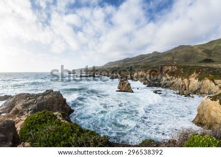 beautiful scene of the California coast with its classic dramatic coastline lined with rocks and cliffs and spring green plants in the foreground - stock photo