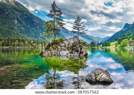 Beautiful scene of trees on a rock island in idyllic scenery at charming Lake Hintersee with blue sky and clouds in summer, Nationalpark Berchtesgadener Land, Upper Bavaria, Germany