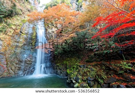 Beautiful Scenery Of A Grand Waterfall Tumbling Down The Rocky Cliff Into Green Pond Surrounded