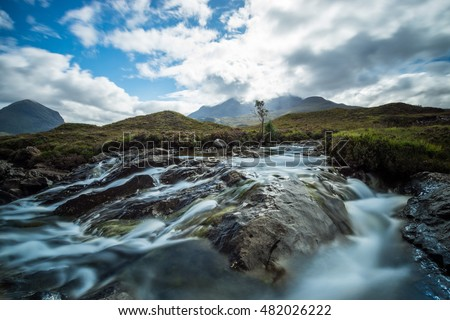 Beautiful scenery of a river coming from a mountain of the scottish Highlands flowing in cascades over solid rocks.