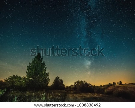 Beautiful scenery of bright night blue sky full of stars above plain meadow
