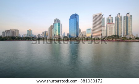 Beautiful scenery of lakeside skyscrapers reflecting on smooth lake water in Benjakiti Park, Bangkok Thailand ~ View of glass curtain walled buildings and their reflections by lakefront before sunrise