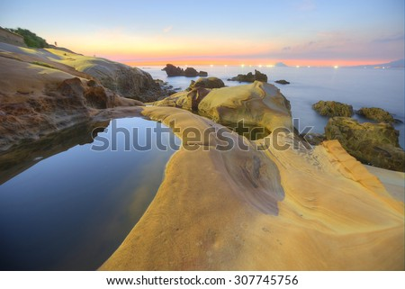 Beautiful scenery of sunrise by rocky coast in northern Taiwan (long exposure effect) With beautiful and tranquil reflection of water ~ - stock photo