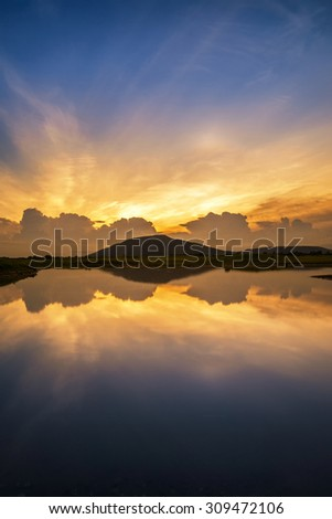 Beautiful scenery sunset sky view of lake and reflection in water. - stock photo