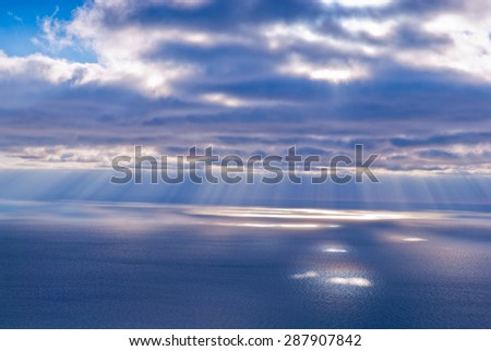 Beautiful scenery with clouds and sunbeams in blue and pink colors - stock photo