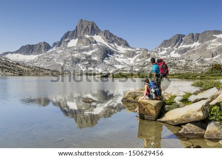 Beautiful scenic landscape with a couple near by a lake and mountains