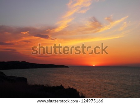 Beautiful scenic landscape with colorful cloudy sky in blue, yellow and red tones at sunset time and silhouette of black cape at foreground in Taman, Krasnodar Krai, Azov sea, Russia, august - 2012 - stock photo