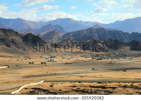 Beautiful scenic view - barren valley against the background of distant colorful mountain range and cloudy blue sky near Leh, Ladakh, Himalaya, Jammu & Kashmir, Northern India - stock photo