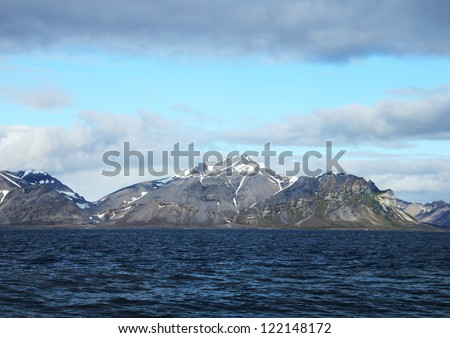 Beautiful scenic view - dark arctic water and distant rugged mountain range covered with snow against the background of dramatic blue sky in Spitsbergen (Svalbard island, Norway), Greenland Sea