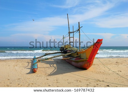 Beautiful scenic view - lonely traditional boat against the background of sea surf and dramatic blue sky in the wild beach of Tangalla, Sri Lanka island, Indian Ocean, South Asia