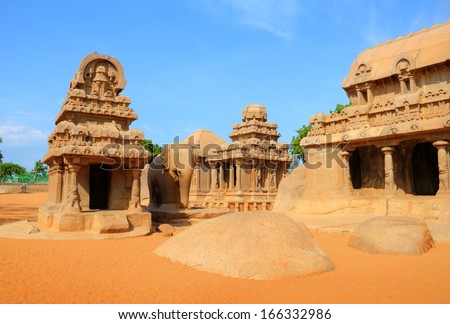 Beautiful scenic view of ancient Hindu stone Temple (UNESCO world heritage site) - Pancha Rathas or Five Chariots - against the background of bright blue sky in Mamallapuram, Tamil Nadu, South India  - stock photo
