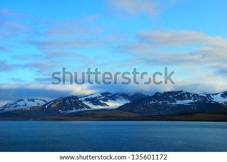 Beautiful scenic view of blue gulf and black mountains with melting snow against background of dramatic evening sky near Barentsburg, Spitsbergen archipelago (Svalbard island), Norway, Greenland sea - stock photo