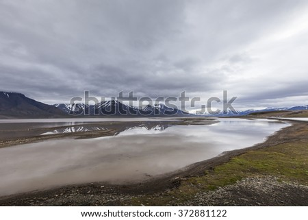 Beautiful scenic view of blue gulf under barren mountain range with melting snow against the background of dramatic evening sky near Barentsburg, Spitsbergen (Svalbard island), Norway, Greenland sea