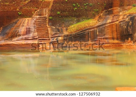 Beautiful scenic view of green pond water against the background of carved wall with scale in Sigiriya Ancient Fortress (Lion's Rock) - UNESCO World Heritage Site, Sri Lanka island, South Asia - stock photo