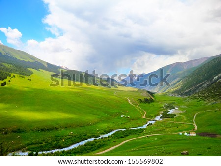 Beautiful scenic view of high mountain valley with meadows and a brook between bright green fields against the background of dramatic cloudy sky of Tien Shan range, Kyrgyzstan, Central Asia - stock photo