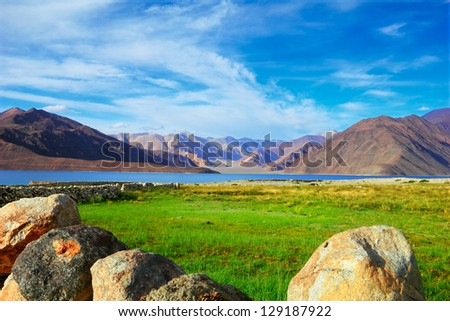Beautiful scenic view of Pangong lake against the background of distant colorful mountain range and cloudy blue sky with green field and well rounded stones, Ladakh, Jammu & Kashmir, Northern India - stock photo