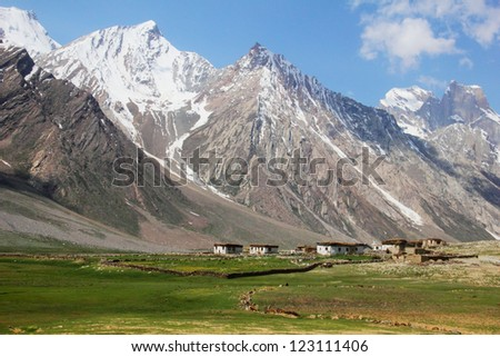 Beautiful scenic view - small traditional Tibet village and green field against the background of high mountain range covered with melting snow and cloudy sky, Ladakh, Jammu & Kashmir, North India - stock photo