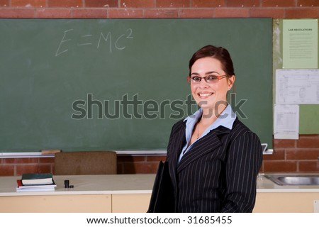 beautiful school teacher standing in classroom