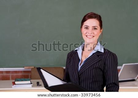 beautiful school teacher standing in classroom - stock photo