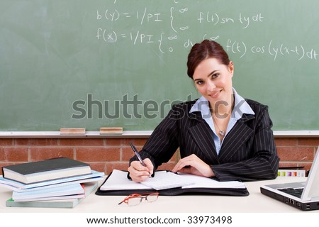 beautiful school teacher working in classroom - stock photo