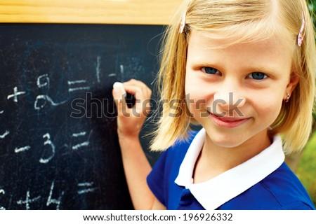 beautiful schoolgirl decides on a blackboard mathematical tasks - stock photo