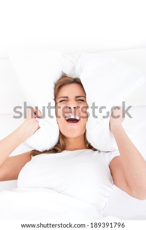 Beautiful screaming woman is lying in bed and covering her ears with pillow. Noise or insomnia concept