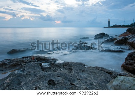 Beautiful sea coast with lighthouse at the sunset