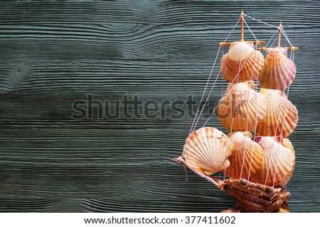 Beautiful sea composition with ship, seashells, copy space on wooden background.Marine still life with toy model of ship made of cockleshells.Travel and adventure concept - stock photo