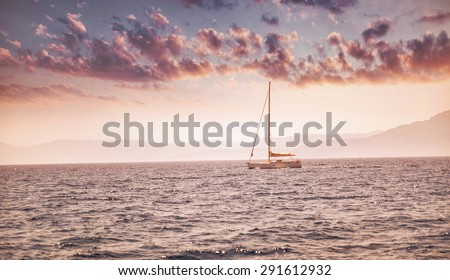 Beautiful sea landscape, sailboat sailing in the distance in mild pink sunset light, romantic vacation in the sea, beauty of summer nature - stock photo