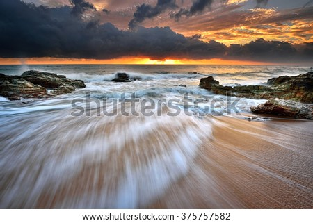 Beautiful seascape at sunrise with motion waves. Nature composition. - stock photo