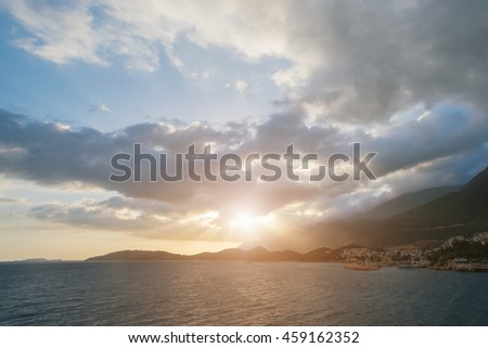 Beautiful seascape: houses with red roofs on the rocky shore by the sea at sunrise or sunset - stock photo