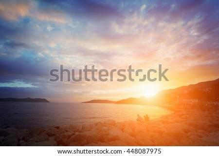 stock photo beautiful seascape people sit on the rocks by the sea at sunrise or sunset toned 448087975 - Каталог — Фотообои «Закаты, рассветы»