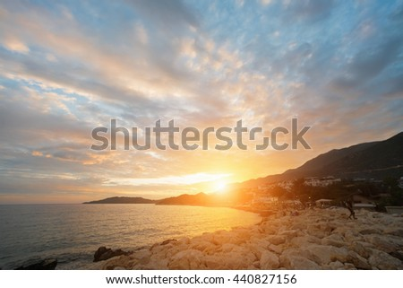 Beautiful seascape: rocky coast with people and buildings at sunrise or sunset - stock photo
