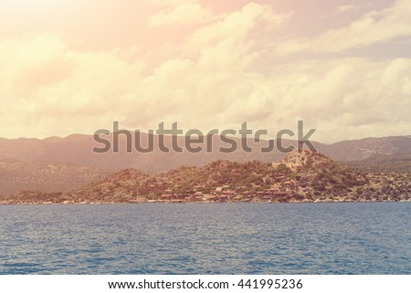 Beautiful seascape: ruins of an ancient fortress and houses with red roofs on a rock by the sea. Toned - stock photo