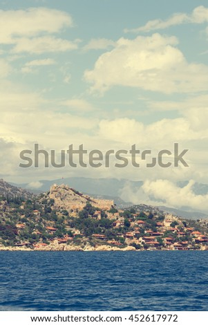 Beautiful seascape: ruins of an ancient fortress and houses with red roofs on a rock by the sea  - stock photo