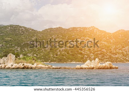 Beautiful seascape: water and rocks in the sunlight - stock photo