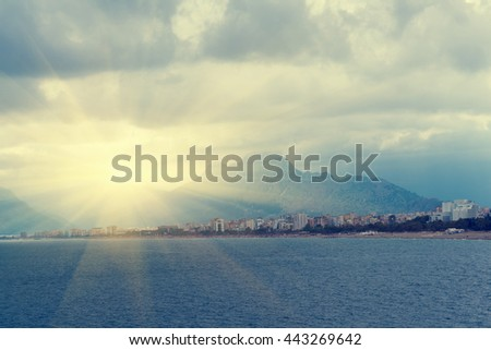 Beautiful seascape: water, resort town, high mountains and cloudy sky in the sunlight. Toned - stock photo