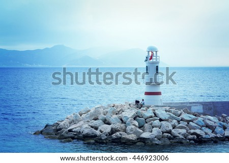 Beautiful seascape: white lighthouse and people on the background of the water and rocks. Toned - stock photo
