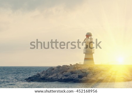 Beautiful seascape: white lighthouse on the background of the water and stones in the sunlight. Toned - stock photo