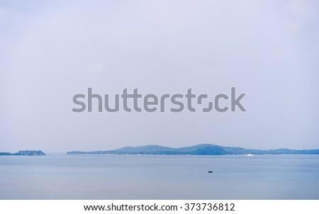 Beautiful seascape with blue island on horizon. - stock photo