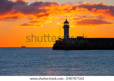 Beautiful seascape with lighthouse on sunrise - stock photo