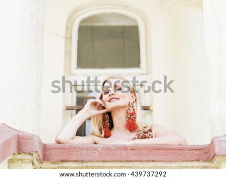 Beautiful seductive cheerful blond woman looking from balcony - stock photo