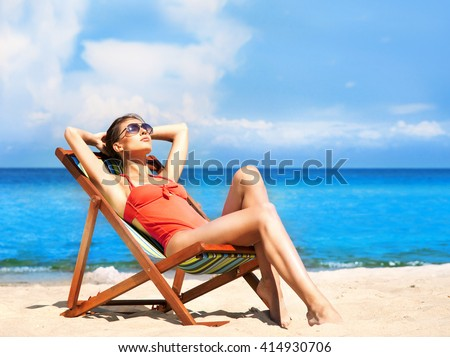 Beautiful, seductive girl in alluring swimsuit getting a suntan while lying in the sun chair on the beach. - stock photo